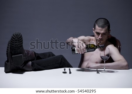Young man pouring wine in broken glass with boots on dinner table