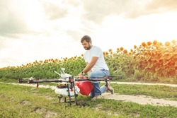 Young man pours fertilizer for irrigation in agriculture drone. Octocopter flight preparation.