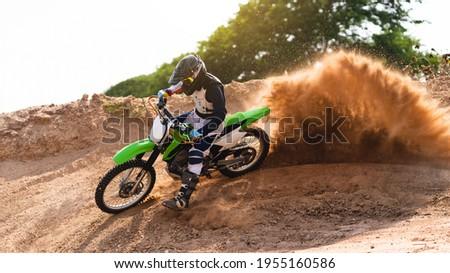 Young man practice riding dirt bike.Splashing sand Stock photo ©