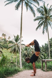 Young man practice yoga rice field jungles during retreat vacation in Bali, stretching, meditation, wellness