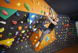 Young man practicing bouldering in indoor climbing gym