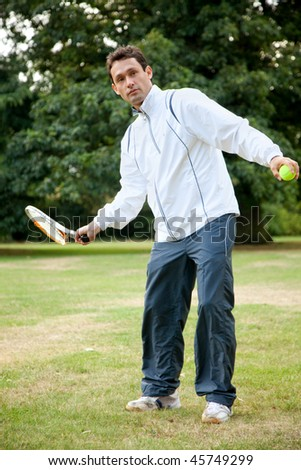 Young man practicing tennis at the park