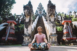 Young man practicing yoga during luxury yoga retreat in Asia, Bali, meditation, relaxation, getting fit, enlightening