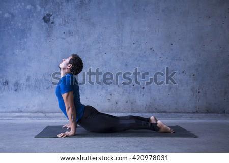 Young man practicing yoga. Upward facing dog, or urdhva mukha svanasana.