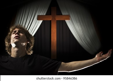 A stock photo of a young man praying with open arms in from of a cross.