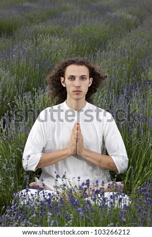 young man praying in a field of lavender in a traditional yoga-posture