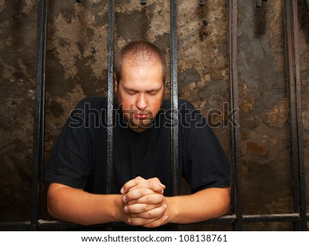Young man praying staying behind the bars