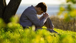 young man praying to God near a tree in the nature bowing his head to his knees with gratitude, male asks for help finding solace in faith, concept religion