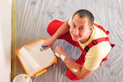 Young Man Preparing To Paint Walls with White Color as Room Renovation at Home. Top Down View on Young Man in Overalls Looks to Camera and Smile. Room Decoration Process