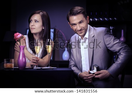 young man present an  engagement ring in the restaurant