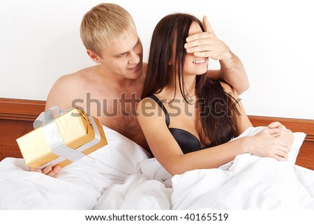 Young man presenting a gift to his girlfriend in bed