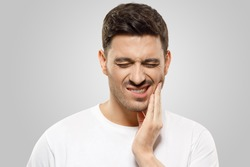 Young man pressing fingers to his jaw, trying to overcome severe toothache, eyes closed, isolated on gray background