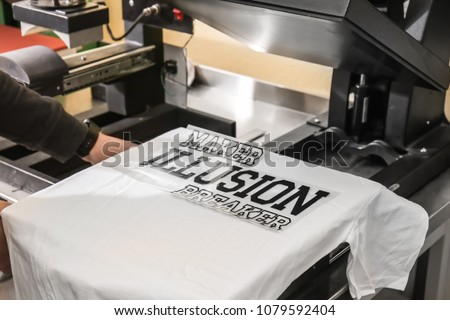 Young man printing on t-shirt at workshop Stock fotó ©