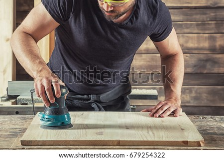 Young Man  processes the board with a random orbit sander in the workshop #679254322