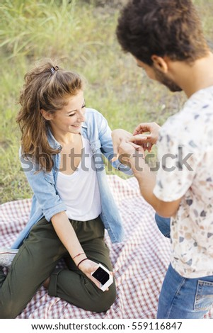 Young man proposing to his fiancee with a beautiful engagement ring #559116847