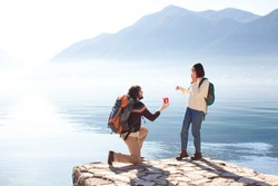 Young man proposing to woman on his knee and giving gift box. Couple at winter sea beach by mountains. Romantic marriage proposal. Lifestyle moment. Happy travelers celebrate engagement outdoor.