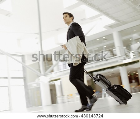 Young man pulling suitcase in modern airport terminal. Travelling guy concept