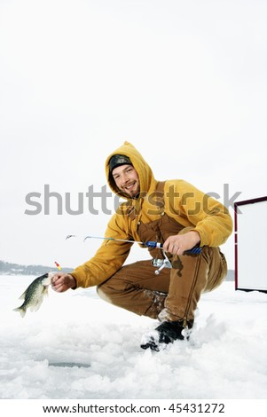Young man pulls a fish out of a hole in the ice. He is holding a fishing rod and wearing snow gear. Vertical shot.