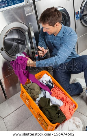 Young man putting clothes in washing machine at laundry #156474602