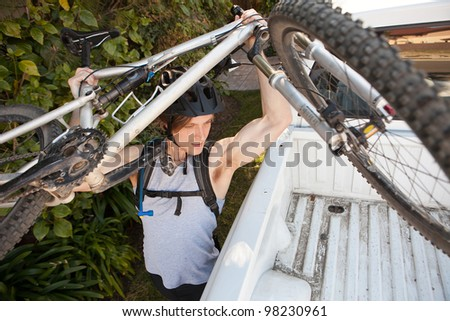 Young man putting his mountain bike in truck