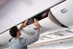 Young man putting luggage into overhead locker on airplane. Traveler placing carry on bag in overhead compartment in aircraft