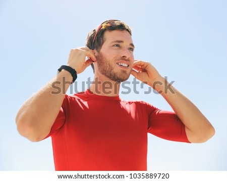 Young man putting on wireless headphone bluetooth connected to smartwatch earphones for fitness run outdoors. Happy active person wearing earbuds for exercise.