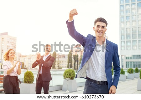 Young man raised his arms up as a sign of victory and success in business. Man against the backdrop of a group of its employees. Concept - business champion. Teamwork. Office workers - winning team. #610273670