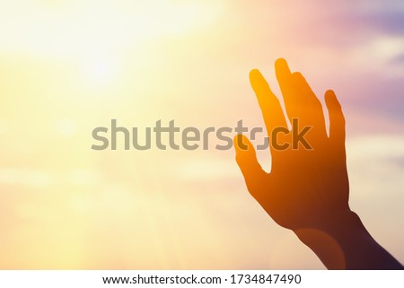 young man raising hands praying at sunset or sunrise light, dreams, freedom and spirituality concept, copy space Foto stock ©