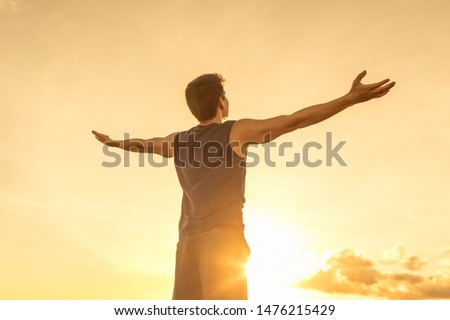 Young man raising his arms up to the sky against the sunset feeling free.  Happiness, freedom, and joy concept.  ストックフォト ©