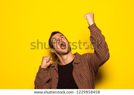 Young man raising his arms with expression of victory. Concept of winning and triumphant person