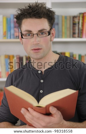 Young man reading a book in library or bookstore