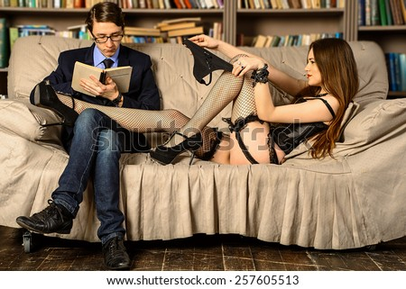 Young man reading a book in the library. Sexy girl clings to a student who is reading a book. Heavy Reading. Sexy girl with panties in her hands looking at the guy who reads the book