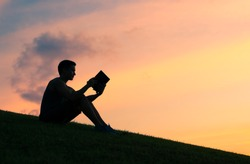 Young man reading a book in the park.