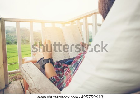 Young man reading a book lying in relaxing bed at terrace with green nature view #495759613