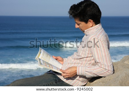 Young man reading a book on a rock with a great view over the sea