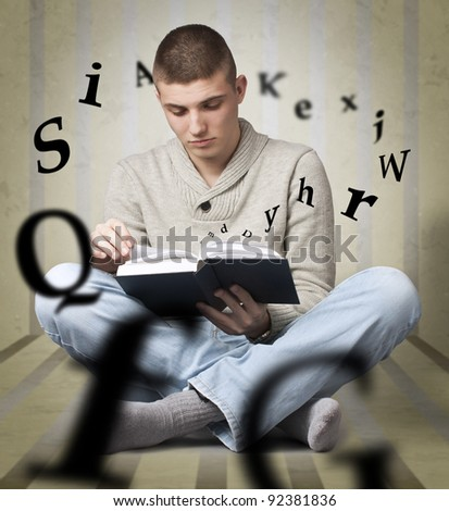 Young man reading a book with alphabet letters coming out of the book