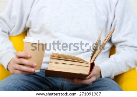 Young man reading book, close-up, on light background