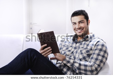 young man reading book in home interior on white background - stock photo