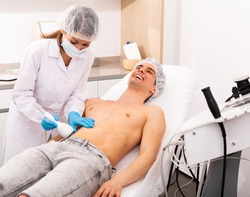 Young man receiving fat reductive skin lifting body treatment on modern equipment at cosmetology clinic, male body care concept