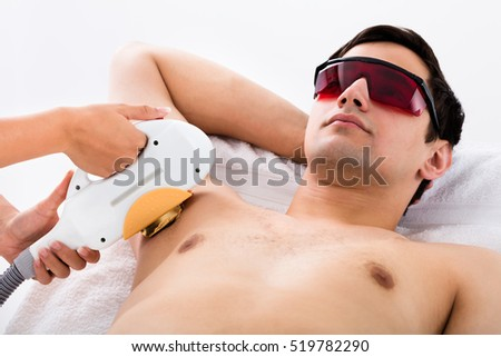 Young Man Receiving Laser Epilation Treatment On Underarms In Spa