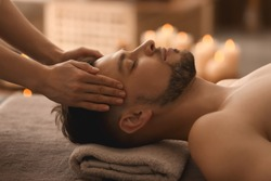 Young man receiving massage at spa salon