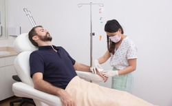 Young man receiving vitamin IV infusion drip in hospital or beauty salon. Healthcare and medicine concept