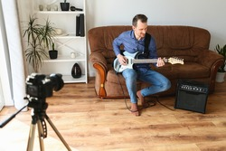 Young man records tutorial video how to play electric guitar, the camera on a tripod indoors, combo amp near. He sits on couch at home. The concept of online learning.