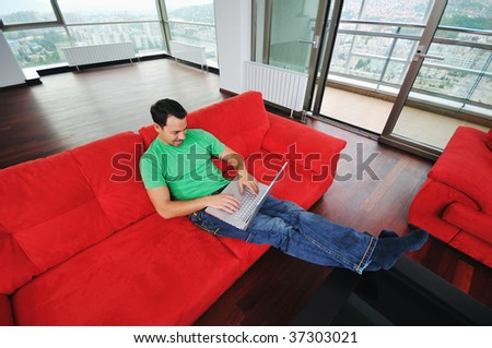 young man relax on red sofa and work on laptop at home indoor