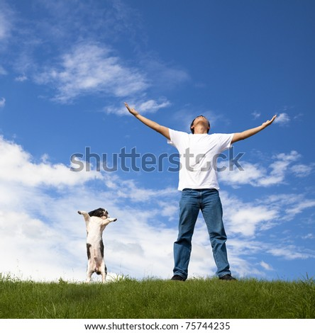 young man relax on the green field with his dog