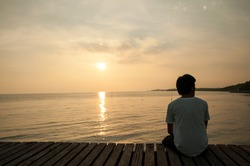 Young man relax siting on sea beach pier looks to right with sunset sky. Conceptual for thinking and looking for concentrate somethings in Summer background with copy space label text banner.