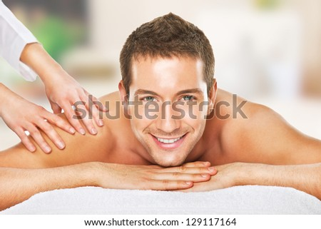 Young man relaxed in spa / Closeup of a man having a back massage