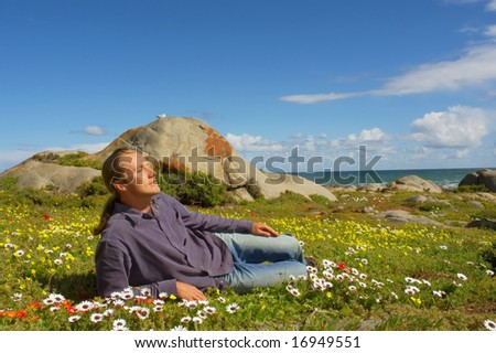 Young man relaxes lying on flower field next to sea. Shot in West Coast Nature Park, near Langebaan, Western Cape, South Africa.