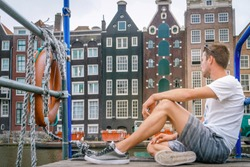 young man relaxing at wtaerfront at the Canals of Amsterdam, Dutch colorful canal house at the capital of the Netherlands Amsterdam