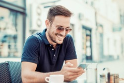 Young man relaxing in cafe,drinking coffee and use his phone.